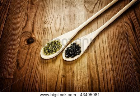 Green soybeans and mexican black beans on wooden background, biologic agriculture
