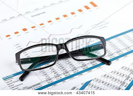 Glasses on contemporary workplace with financial papers