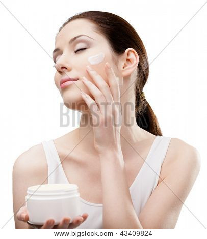 Woman putting on emollient cream from container on face, isolated on white. The pursuit of beauty