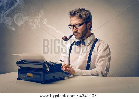 handsome journalist writing with typewriter
