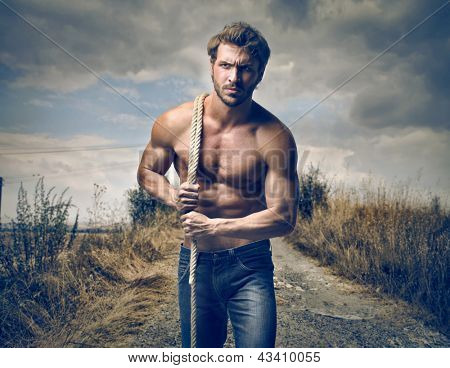 strong handsome man with rope
