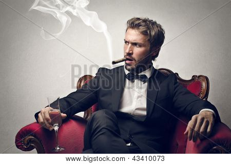 handsome boss sitting on the armchair smokes cigar