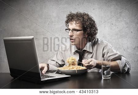 young businessman works with laptop while eats spaghetti