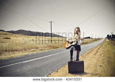 young woman playing guitar on the road