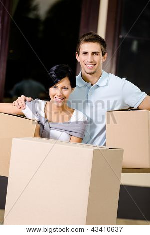 Happy couple carrying pasteboard containers while moving to new house