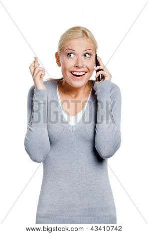 Smiley woman speaking on phone with her fingers crossed, isolated on white