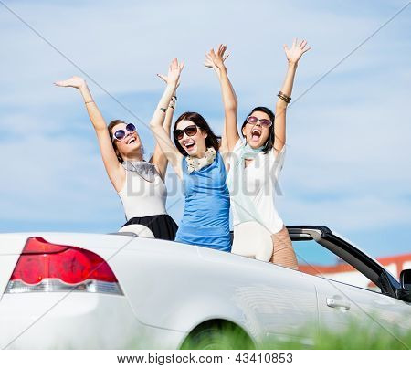 Group of girls stands in the automobile with hands up. Happy journey of joyful teenagers