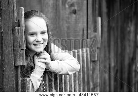 Portrait of emotional girl standing near vintage rural fence, black-and-white photo.