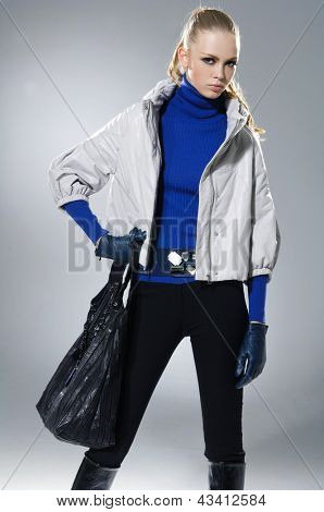 High fashion model with bag posing on light background