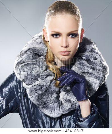 fashion model in fur coat clothes posing on gray background