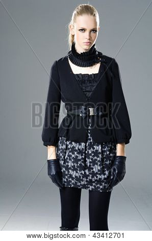 fashion model in modern clothes wearing gloves posing
