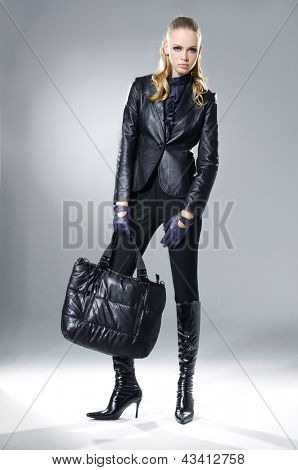 full-length fashion girl with handbag posing on light background