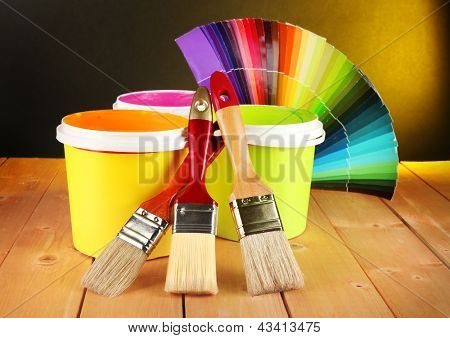 Paint pots, paintbrushes and coloured swatches on wooden table on dark yellow background