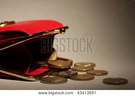 female red wallet with coins on grey background