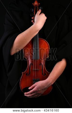 Violin in hands on black background