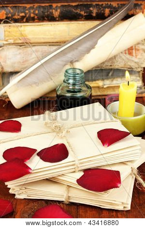 Stacks of old letters with dried rose petals on wooden table