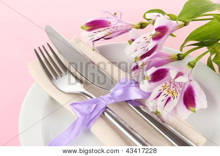 Festive dining table setting with flowers on pink background