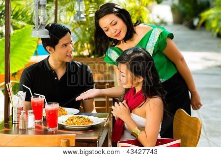 Asian man and woman in restaurant are being served food by the waitress