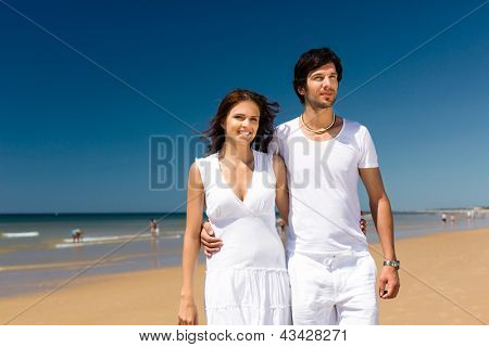 Playful couple on the ocean beach enjoying their summer vacation, they walking arm in arm