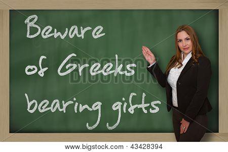 Teacher Showing Beware Of Greeks Bearing Gifts On Blackboard