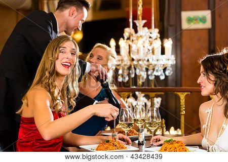 Good friends for lunch in a fine restaurant, waiter spices the dinner, he using a spice mill