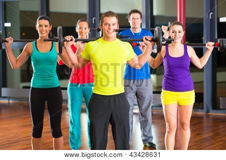 group of young sport people training with barbell at a gym for better fitness