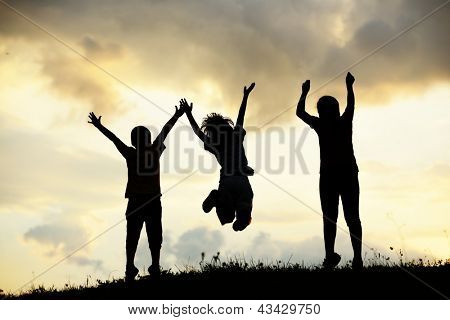 Active group of kids spending happy time on summer sunset at meadow