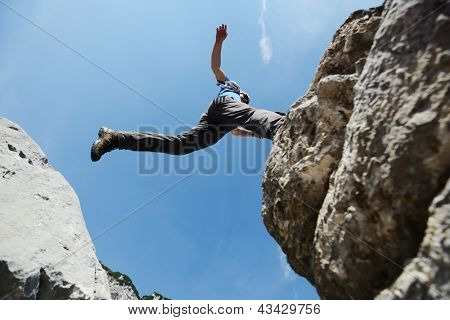Hiking man jumping over the mountains to success