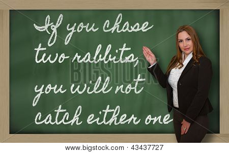 Teacher Showing  If You Chase Two Rabbits, You Will Not Catch Either On Blackboard
