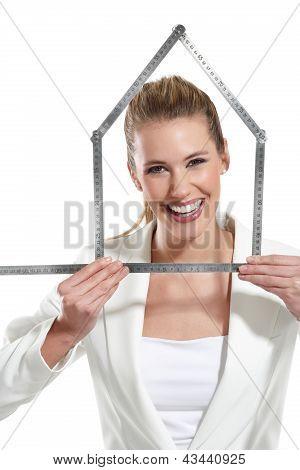 Bela mulher feliz mostrando um símbolo de casa