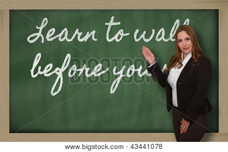 Teacher Showing Learn To Walk Before You Run On Blackboard