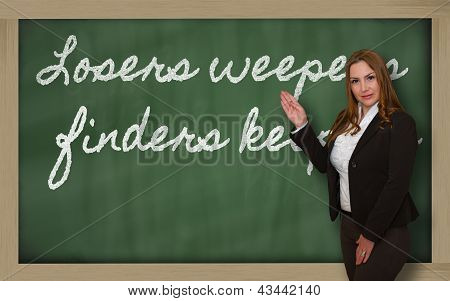 Teacher Showing Losers Weepers, Finders Keepers_blackboard On Blackboard