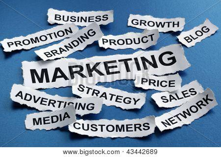 Marketing concept torn newspaper headlines reading marketing, strategy, branding, advertising etc