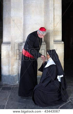 Mature nun kissing the ring of a cardinal in a medieval church