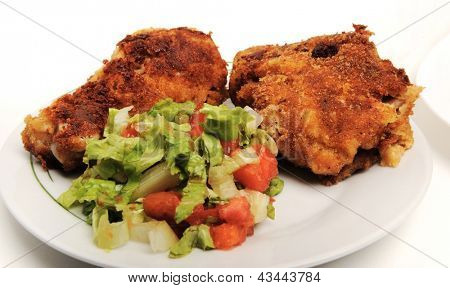 chicken wings on plate with green salad and tomato