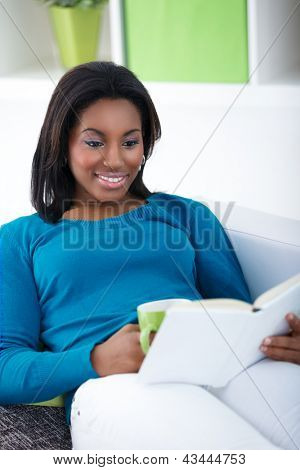 Smiling black woman reading interesting book