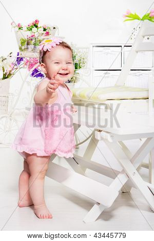 Lovely emotional toddler girl in pink dress