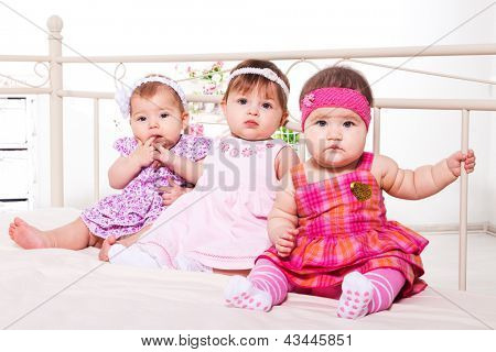 Group of baby girls in lovely dresses sitting on bed