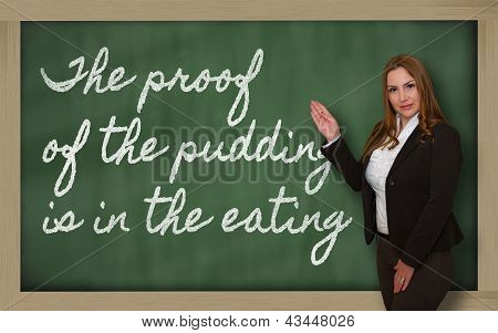 Teacher Showing The Proof Of The Pudding Is In The Eating On Blackboard