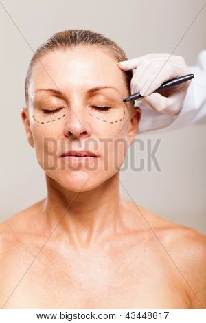 beautician draw correction line on middle aged woman face before plastic surgery