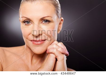 portrait of beautiful mid aged woman close up over black background