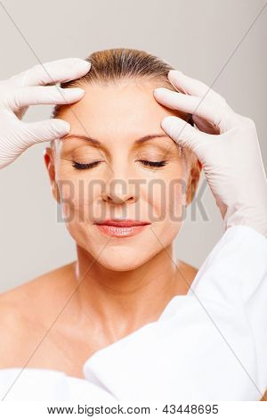 doctor doing skin check on senior woman before cosmetic surgery