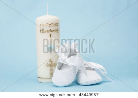 Christening candle for a boy with white baby booties on blue background