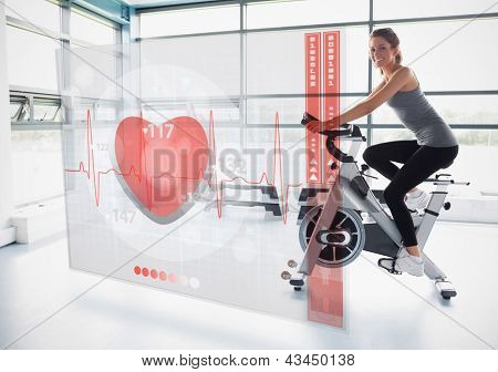 Young girl doing exercise bike with futuristic interface showing electrocardiogram