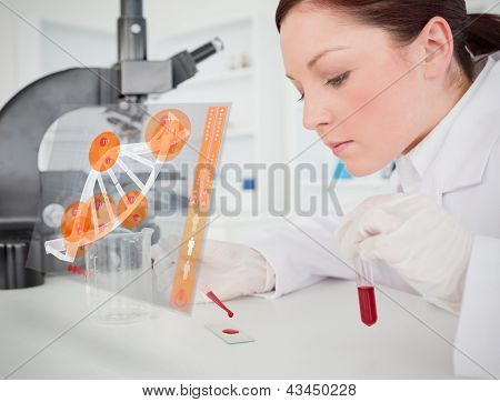Scientist pouring drop of blood onto glass with futuristic interface in front of her