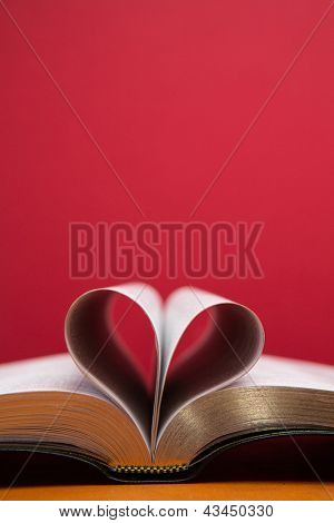 Embossed pages of book folded to make heart on red background