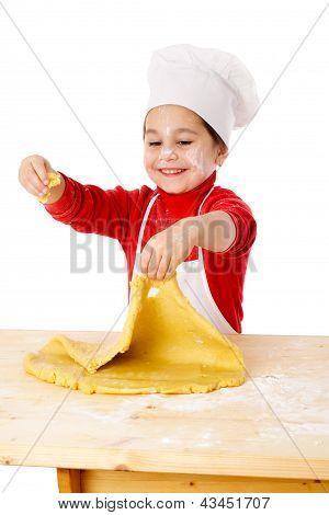 Little girl kneading the dough