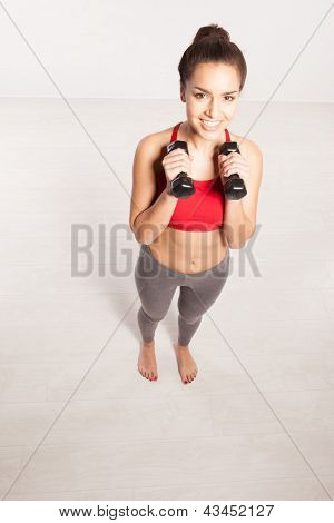 A young woman in workout gear holding two small dumbbells