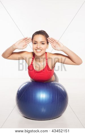 Smiling woman doing pilates exercises, balancing on top of a gym ball with her hands raised facing the camera