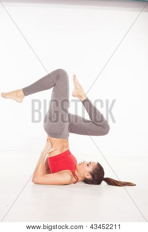 Healthy woman doing Shoulder stands Yoga pose
